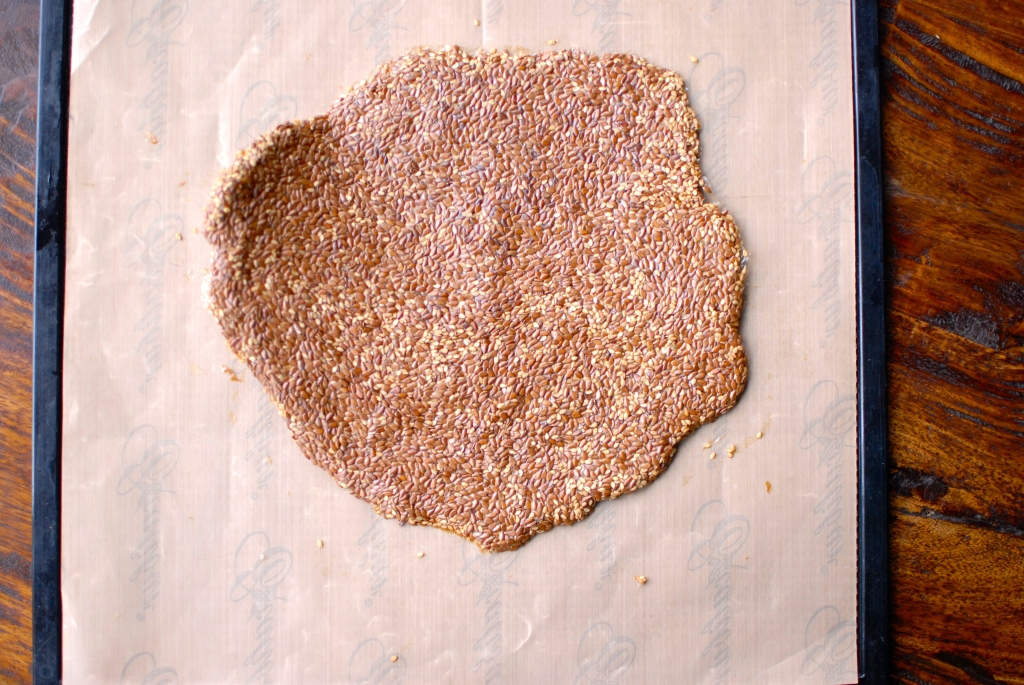 healthy sesame flax seed crackers rolled out on non-stick dehydrator mat